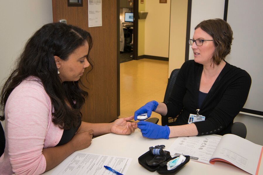 woman taking blood sugar levels from another woman