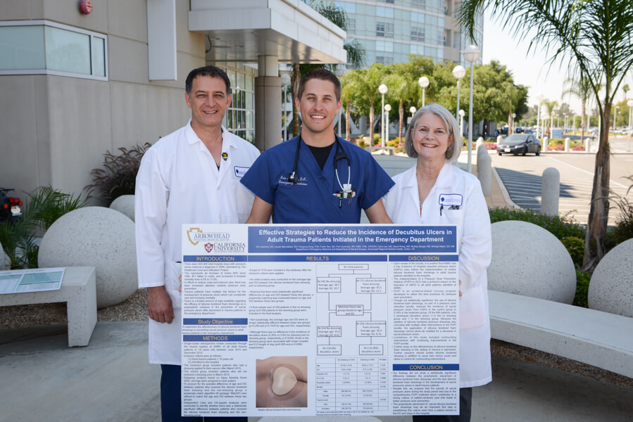three doctors standing with large study poster